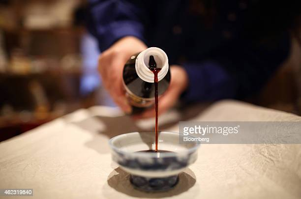 A Yagisawa Shouten Co employee pours soy sauce into a dish in an arranged photograph at the company's headquarters in Rikuzentakata Iwate prefecture...