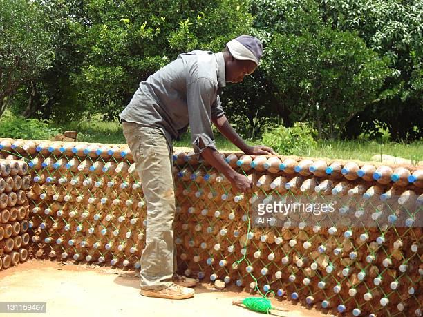 Yahaya Musa 19year old local mason Yahaya inspects a wall of stacks of sandfilled plastic bottles in Sabongarin Yelwa village near northern Nigerian...