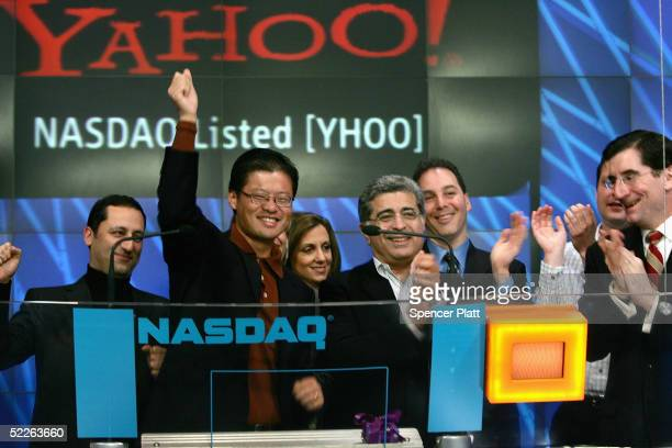 Yahoo cofounder Jerry Yang raises his fist after ringing the opening bell at the NASDAQ with other Yahoo employees to celebrate the 10th anniversary...
