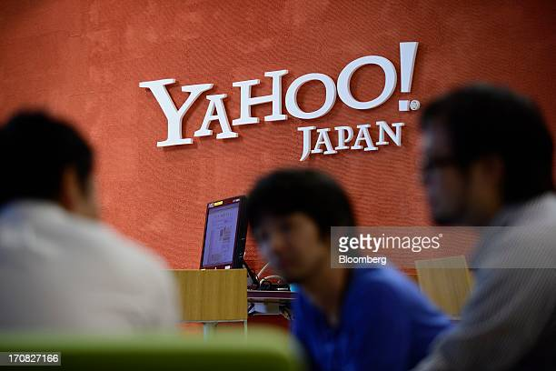 Yahoo Japan Corp. Employees speak to a customer in front of the company's logo at its headquarters in Tokyo, Japan, on Tuesday, June 18, 2013. Yahoo...