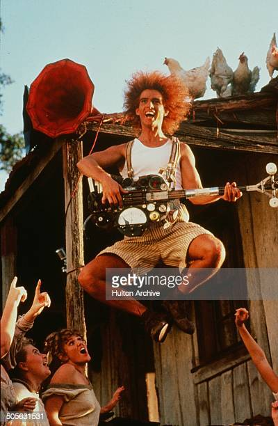 Yahoo Serious jumps as he plays a guitar in a scene from the Warner Bros movie 'Young Einstein' circa 1988