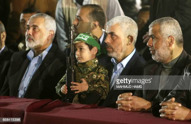 TOPSHOT Yahya Sinwar the new leader of the Hamas Islamist movement in the Gaza Strip and senior political leader Ismail Haniyeh sit next to the son...