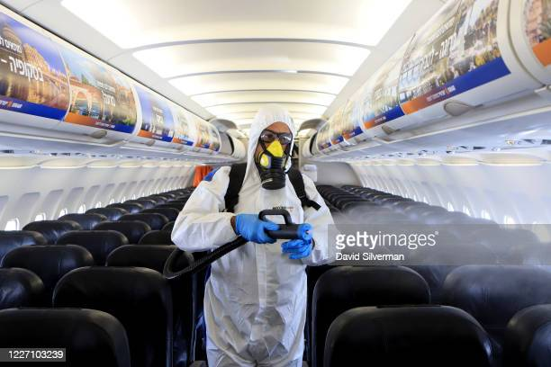 Yair Badash, a maintenance manager at the Israeli low-cost ariline Israir, wears his PPE as he disinfects an aircraft between flights at Ben Gurion...