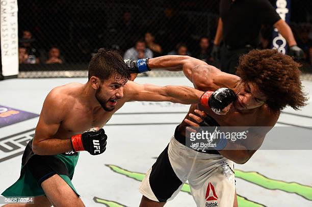 Yair Rodriguez of Mexico punches Alex Caceres in their featherweight bout during the UFC Fight Night event at Vivint Smart Home Arena on August 6...