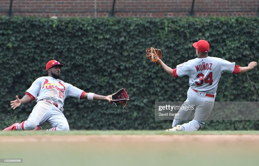 Yairo Munoz #34 of the St. Louis Cardinals makes a catch on Jason Heyward #22 of the Chicago Cubs as Dexter Fowler #25 of the St. Louis Cardinals slides during the seventh inning on July 22, 2018 at Wrigley Field in Chicago, Illinois.