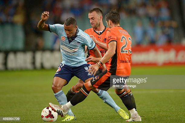 Yairo Yau of Sydney is tackled by Ivan Franjic and Dimitri Petratos of the Roar during the round 12 ALeague match between Sydney FC and Brisbane Roar...