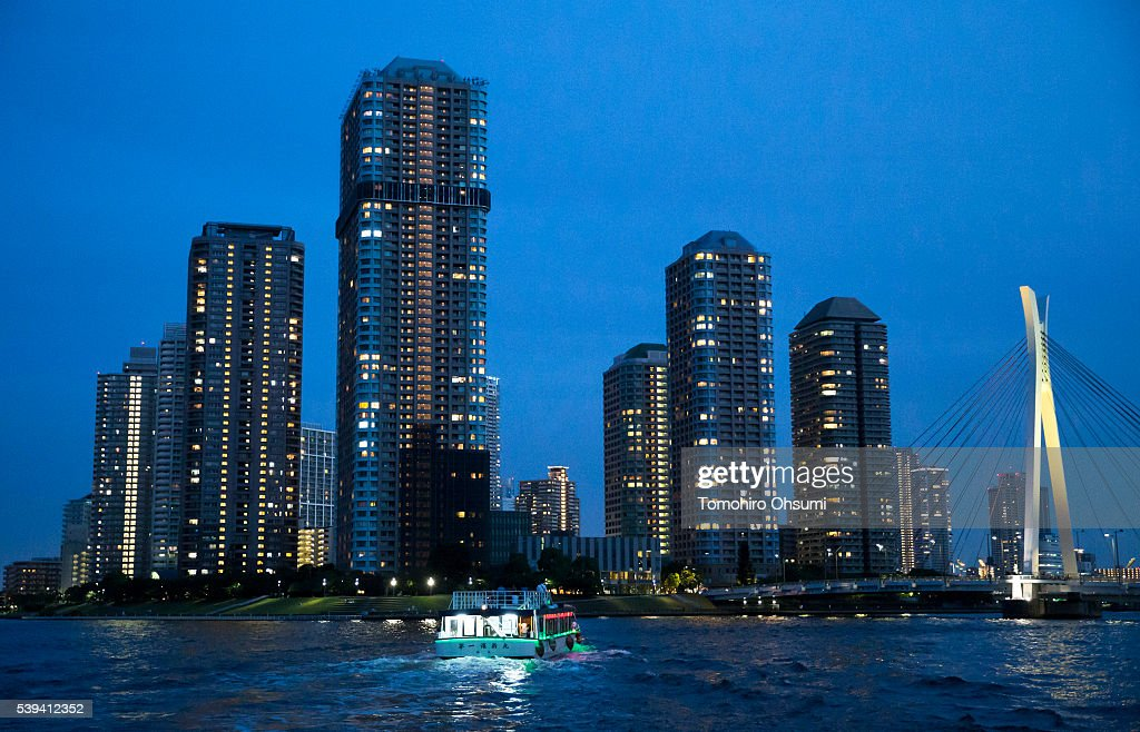 A yakatabune, or traditional low barge style boat, sails on the Sumida River as buildings stand illuminated at night on June 11, 2016 in Tokyo, Japan. About 35 companies operate over 100 yakatabune boats in Tokyo offering services such as dinner or karaoke inside the boats while cruising in Tokyo's bay area, according to the Tokyo Yakatabune Association.