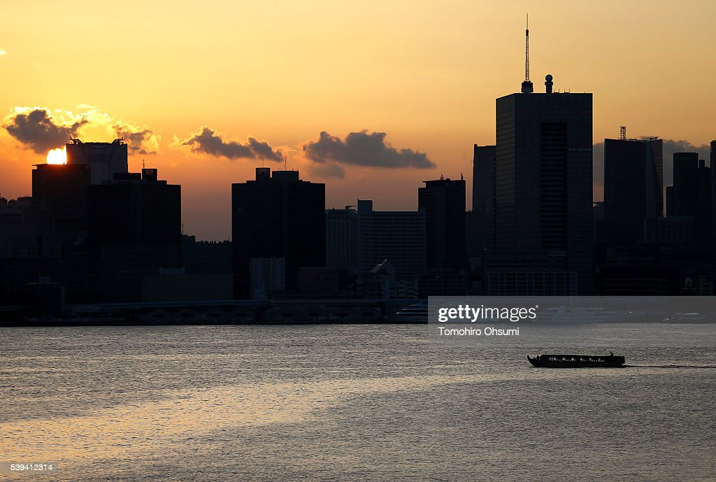 A yakatabune, or traditional low barge style boat, sails past commercial buildings on the Sumida River at dusk on June 10, 2016 in Tokyo, Japan. About 35 companies operate over 100 yakatabune boats in Tokyo offering services such as dinner or karaoke inside the boats while cruising in Tokyo's bay area, according to the Tokyo Yakatabune Association.