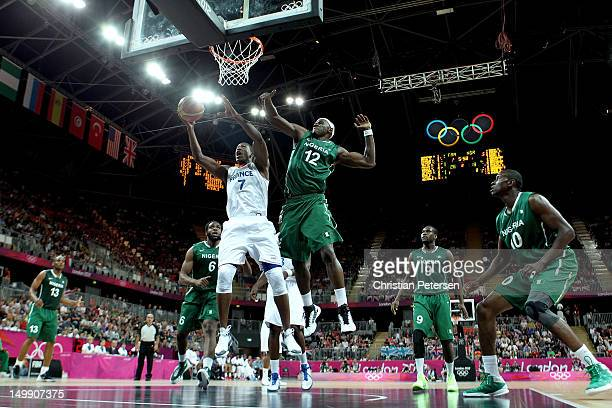Yakhouba Diawara of France drives for a shot attempt against Ejike Ugboaja of Nigeria during the Men's Basketball Preliminary Round match on Day 10...