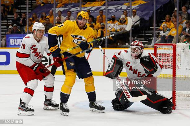 Yakov Trenin of the Nashville Predators tries to deflect a puck in front of goalie Alex Nedeljkovic of the Carolina Hurricanes during the first...