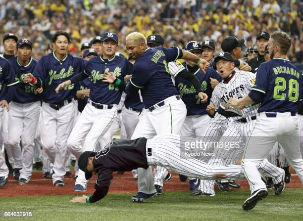 Yakult Swallows outfielder Wladimir Balentien shoves over Hanshin Tigers coach Akihiro Yano during a benchclearing scuffle after a teammate was hit...