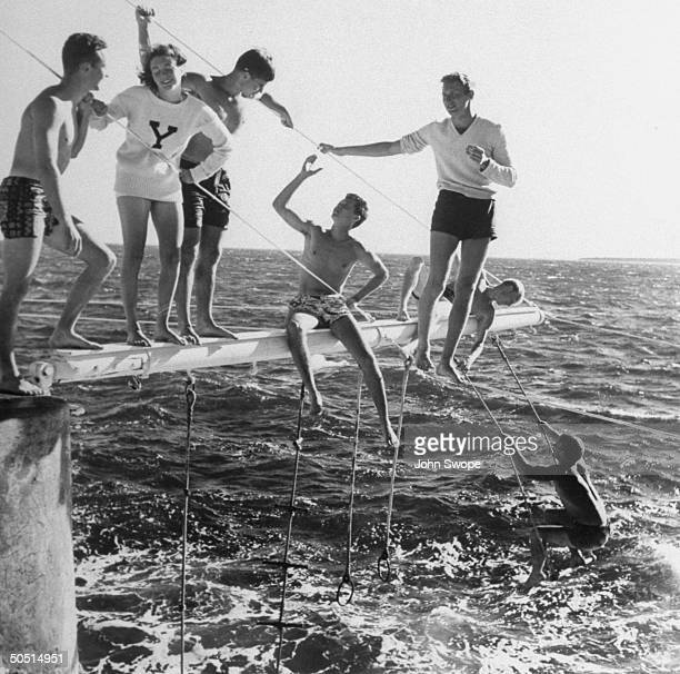 Yale boys and Smith girl on trapeze boom over the water