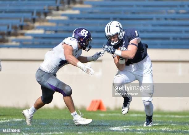 Yale Bulldogs wide receiver Michael Siragusa Jr runs the ball up the field while defended by Holy Cross Crusaders linebacker Ryan Brady during the...