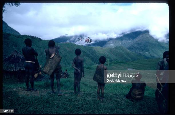 Yalli tribespeople watch as a missionary helicopter prepares to land June 21, 1980 in Irian Jaya, Indonesia. Missionaries render assistance and aid...