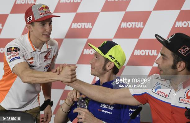 Yamaha biker Valentino Rossi of Italy looks at Honda biker Marc Marquez of Spain as he shakes hands with Ducati bikder Danilo Petrucci of Italy...