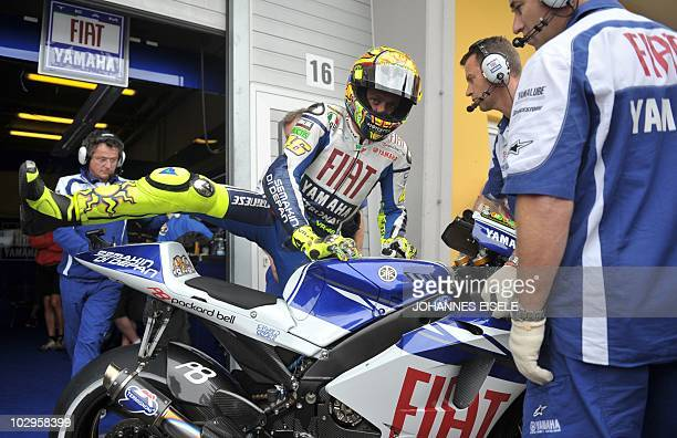 Yamaha driver Valentino Rossi of Italy gets on his bike ahead of the MotoGP race of the Moto Grand Prix of Germany at Sachsenring Circuit on July 18...