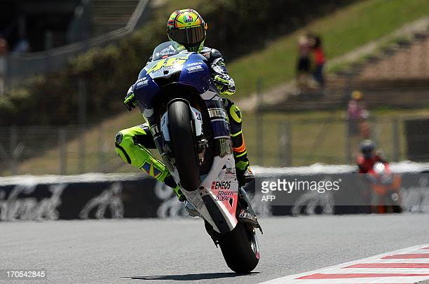 Yamaha Factory Racing's Italian rider Valentino Rossi performs a wheelie during the second MotoGP free practice of the Catalunya Grand Prix at the...