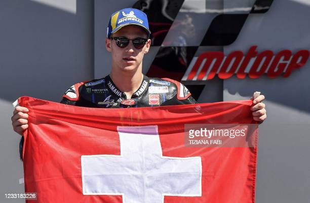 Yamaha French rider Fabio Quartararo poses with a Swiss national flag in tribute to Swiss Moto3 rider Jason Dupasquier, who died aged 19 from...