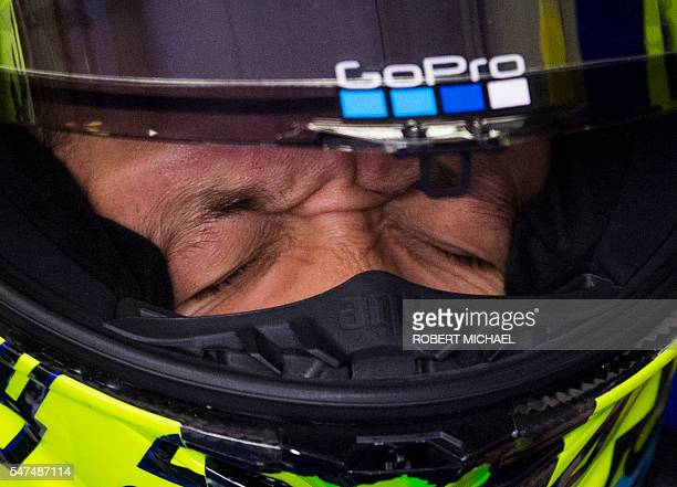 Yamaha's Italian motorcycle road racer Valentino Rossi adjusts his helmet as he sits in the pits prior the first training session of the Moto GP of...