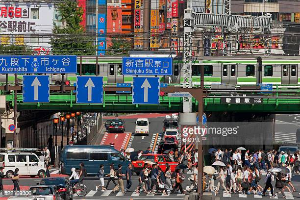 A Yamanote Line Train Crosses Over Pedestrians and Traffic at Shinjuku Station in Tokyo, Japan