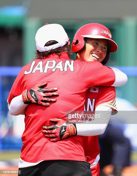 Yamato Fujita of Team Japan gets a hug from head coach Reika Utsugi after Fujita hit a two-run home run in the fourth inning against Team Australia...
