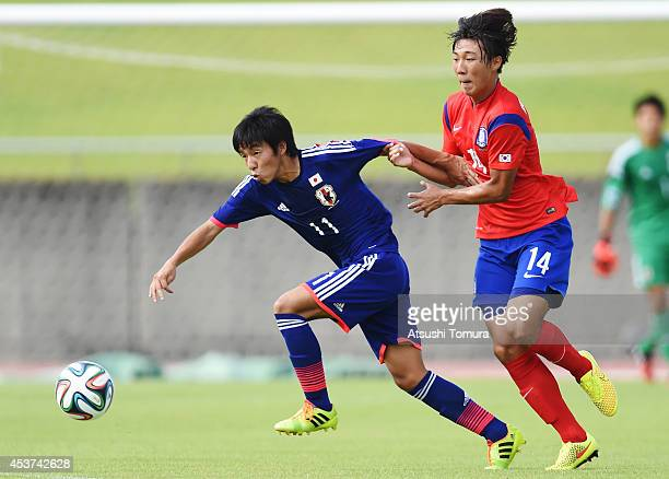 Yamato Ochi of Japan holds off a challenge from Kiwook Hwang of South Korea in the U19 match between South Korea and Japan during SBS Cup...