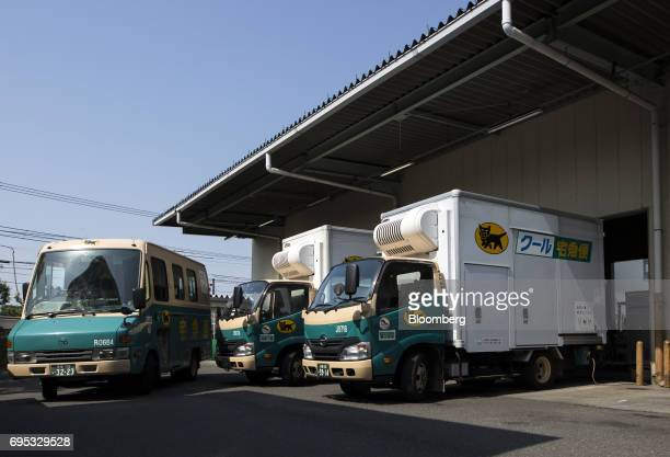 A Yamato Transport Co delivery truck left drives past other trucks parked outside a Yamato branch in Musashimurayama Tokyo Japan on Tuesday May 30...
