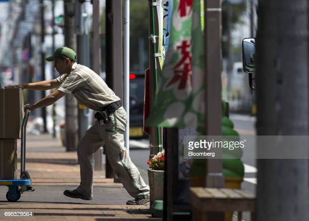 A Yamato Transport Co driver pushes a cart loaded with parcels for distribution in Musashimurayama Tokyo Japan on Tuesday May 30 2017 In April Yamato...