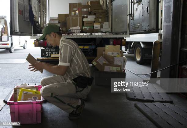 A Yamato Transport Co driver sorts packages ahead of distribution at a Yamato branch in Musashimurayama Tokyo Japan on Tuesday May 30 2017 In April...