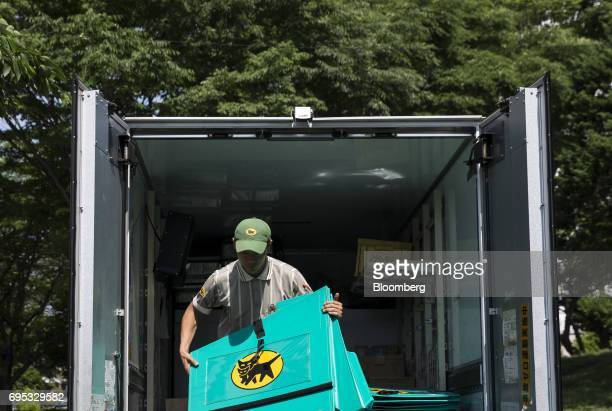 A Yamato Transport Co driver unloads delivery carts from a truck ahead of distribution outside a residential building in Musashimurayama Tokyo Japan...