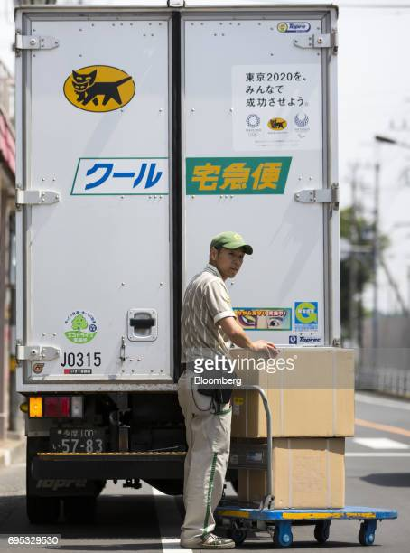 A Yamato Transport Co driver waits to cross a road as he pushes a cart loaded with parcels for distribution in Musashimurayama Tokyo Japan on Tuesday...