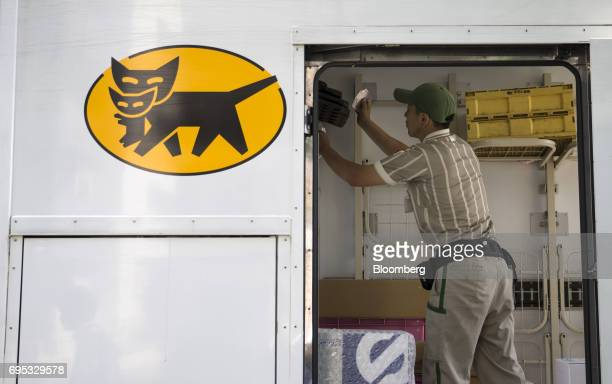 A Yamato Transport Co driver works on a delivery truck at a Yamato branch in Musashimurayama Tokyo Japan on Tuesday May 30 2017 In April Yamato...