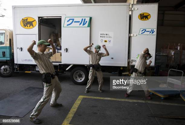 Yamato Transport Co drivers stretch in front of a delivery truck before departing a Yamato branch in Musashimurayama Tokyo Japan on Tuesday May 30...