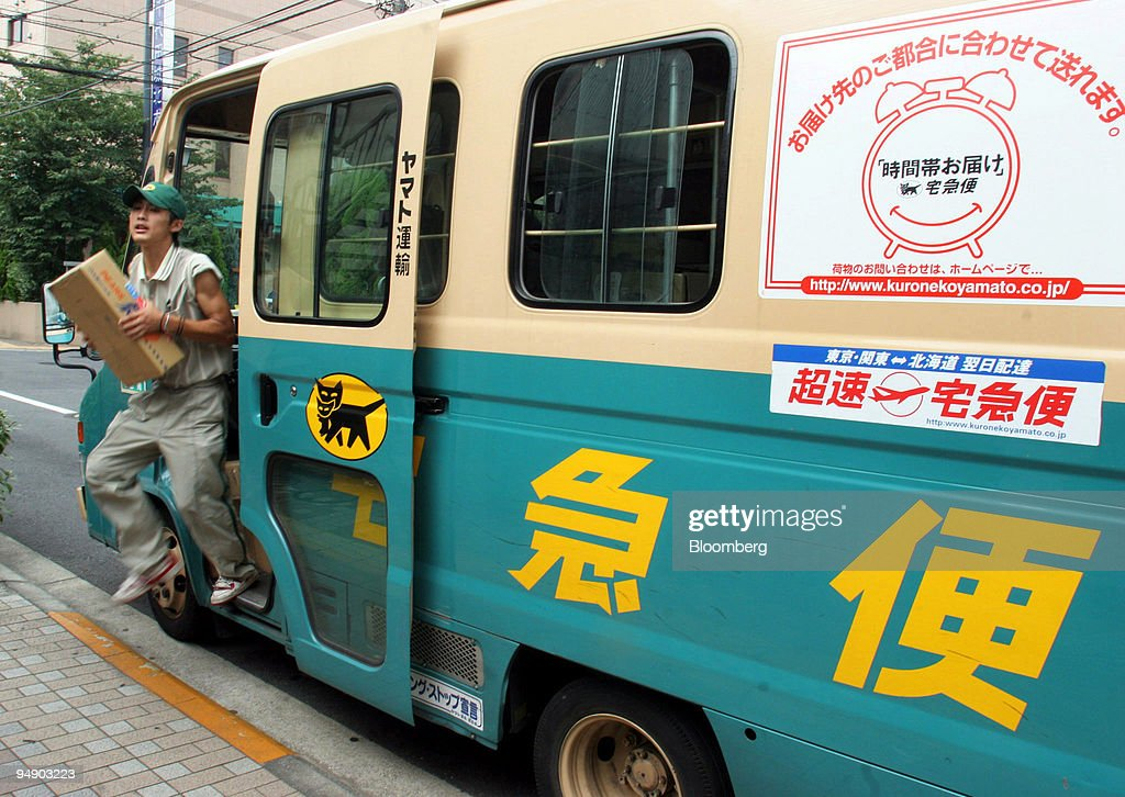 A Yamato Transport Co. employee jumps out of his delivery va : News Photo