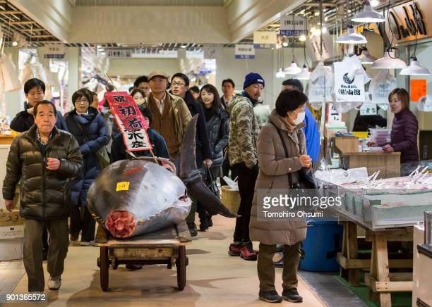 Yamayuki Group employees carry the highest priced fresh bluefin tuna auctioned from the year's first auction at Tsukiji Market on January 5 2018 in...