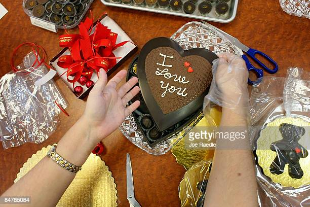 Yamirka Esteves puts a Valentine's Day chocolate gift pack together at Schakolad Chocolate Factory on February 13, 2009 in Davie, Florida. Chocolate,...