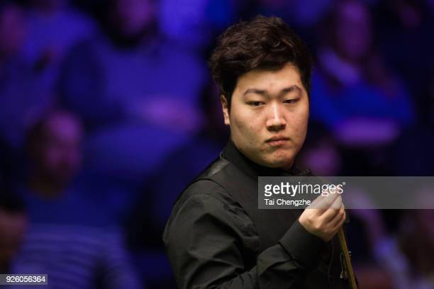 Yan Bingtao of China chalks the cue during his fourth round match against Matthew Stevens of Wales on day four of 2018 ManBetX Welsh Open at...