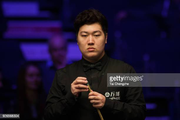 Yan Bingtao of China chalks the cue during his quarterfinal match against Barry S Hawkins of England on day five of 2018 ManBetX Welsh Open at...