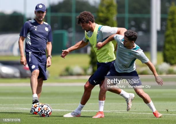 Yan Couto and Phillipe Sandler of Manchester City in action during a training session at Manchester City Football Academy on July 20, 2021 in...