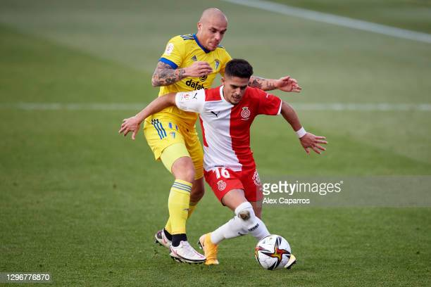 Yan Couto of Girona FC battles for the ball with Jorge Marcos Pombo of Cadiz CF during the Copa del Rey round of 32 match between Girona FC and Cadiz...