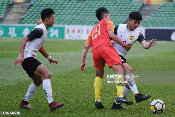 Yan Dinghao of China holds on to Aphixay Thanakhanty of Laos during the AFC U23 Championship qualifier between China and Laos at Shah Alam Stadium on...