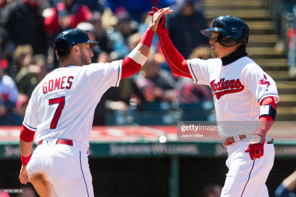 Yan Gomes #7 celebrates with Brandon Guyer #6 of the Cleveland Indians after both scored on a home run by Guyer during the second inning against the Seattle Mariners at Progressive Field on April 29, 2018 in Cleveland, Ohio.