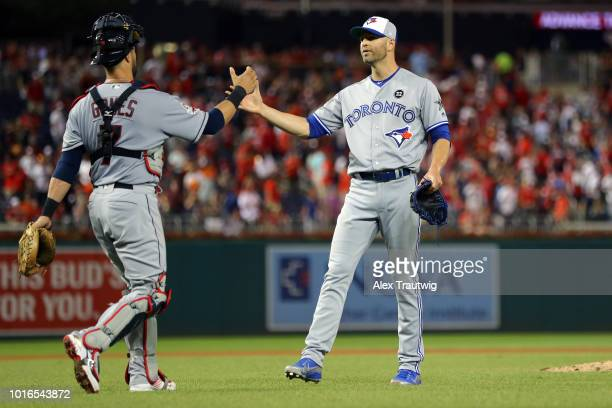 Yan Gomes of Cleveland Indians celebrates with JA Happ of the Toronto Blue Jays after the last out to defeat the National League 86 in the 89th MLB...