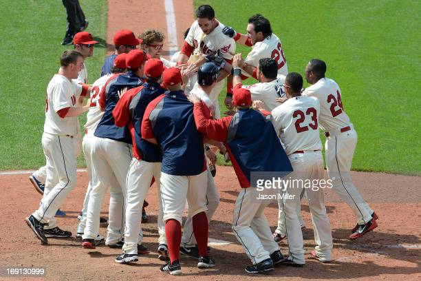 Yan Gomes of the Cleveland Indians leaps into a scrum of teammates at home plate after Gomes hit a walkoff three run home run to beat the Seattle...