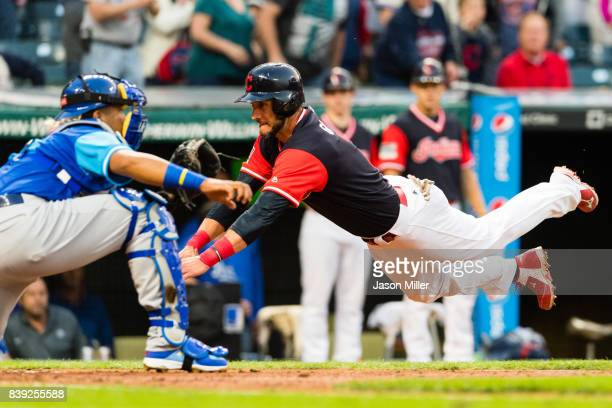 Yan Gomes of the Cleveland Indians scores on a double by Giovanny Urshela as catcher Salvador Perez of the Kansas City Royals tries to make the tag...