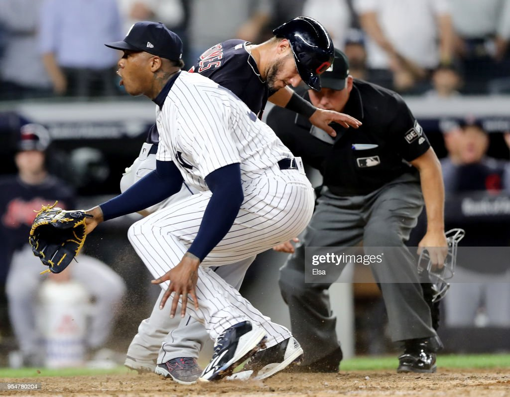 Yan Gomes #7 of the Cleveland Indians scores on a wild pitch to teammate Jason Kipnis as Aroldis Chapman #54 of the New York Yankees reacts after trying to make the tag in the ninth inning at Yankee Stadium on May 4, 2018 in the Bronx borough of New York City.