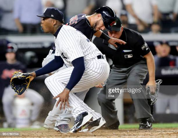 Yan Gomes of the Cleveland Indians scores on a wild pitch to teammate Jason Kipnis as Aroldis Chapman of the New York Yankees reacts after trying to...