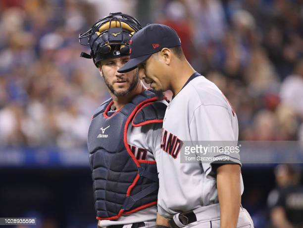 Yan Gomes of the Cleveland Indians talks to Carlos Carrasco after getting the last out of the fourth inning during MLB game action against the...