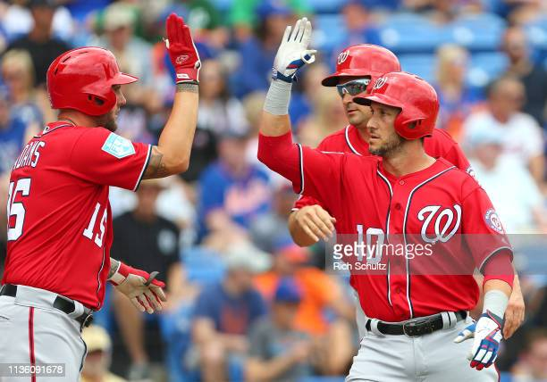 Yan Gomes of the Washington Nationals celebrates his home run with Matt Adams and Ryan Zimmerman against the New York Mets during a spring training...