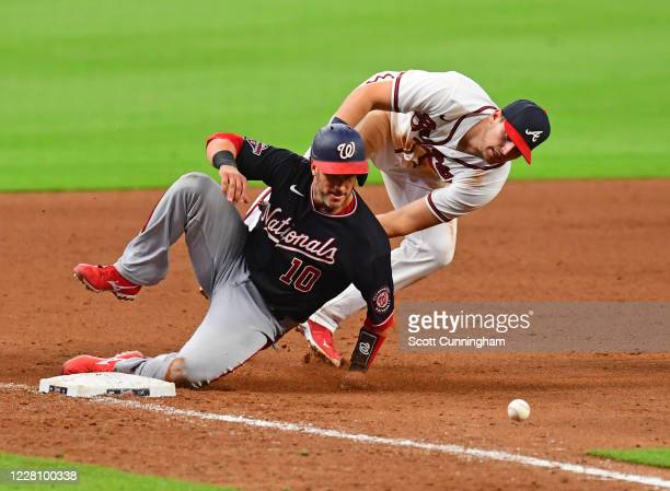 Yan Gomes of the Washington Nationals is safe at third base as the ball eludes Austin Riley of the Atlanta Braves during the ninth inning at Truist...